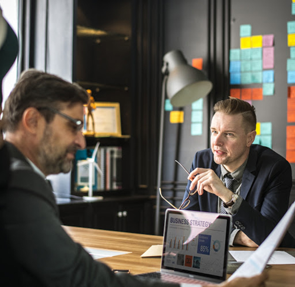 Two businessmen in suits discussing a business plan